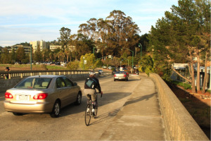A motorist and bicyclist sharing the road on the existing bridge. The replacement bridge will have barrier-protected multi-use paths on both sides in addition to dedicated bike lanes.